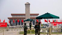 Paramilitary policemen stand guard at the Monument to the People's Heroes at Tiananmen Square near the Great Hall of the People in Beijing