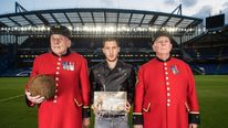 Chelsea and Belgium footballer Eden Hazard with Chelsea Pensioners Steve Lovelock (left) - holding the Loos Football - and Dave Thomson (right) at Stamford Bridge football ground, London