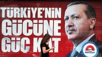 A woman walks past an election poster of Turkey's PM and presidential candidate Erdogan in Istanbul