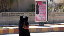 Women in Syria walk past a billboard that urges females to wear a hijab