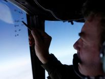 Squadron leader Brett McKenzie marks the name of another search aircraft in the search for the plane