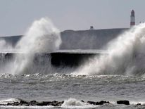 Waves crash against the promenade in Marsden near the Souter Lighthouse