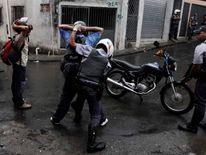 Police officers frisk residents of the Brasilandia favela
