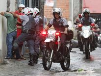 Police officers frisk residents of the Brasilandia favela as fellow officers ride past on their motorcycles