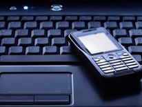 Generic phone hacking image - mobile phone sits on laptop