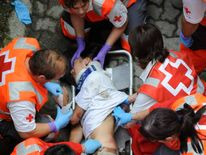 Medics attend to a man injured during the San Fermin Festival bull run in Pamplona
