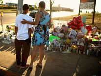 Visitors to a makeshift memorial to the vicitims of mass shooting in Aurora
