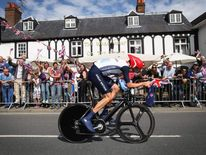 Bradley Wiggins of Great Britain cycles past a pub in Esher during the Men's Individual Time Trial Road Cycling