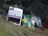 Fireman stand near a coach which has crashed into a tree on the A3 road on September 11, 2012 near Hindhead, England.