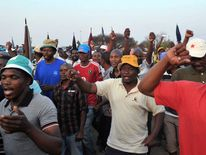 Striking miners gesture and chant