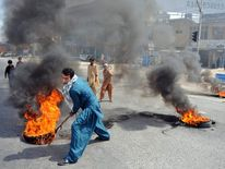 A Pakistani demonstrator drags burning tyres on a street during a protest against an anti-Islam film in Rawalpindi on September 21, 2012.