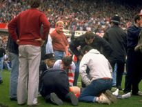 Fans treat an injured supporter