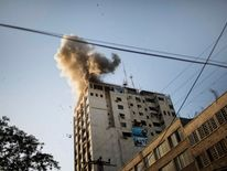 Smoke billows as debris flies from the explosion at the local Al-Aqsa TV station in Gaza City