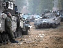 An Israeli soldier stands near tanks in a deployment area on November 19 on Israel's border with the Gaza Strip.