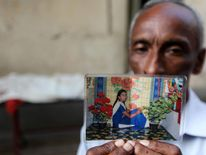 Bangladeshi Mohammad Ali holds up a photograph of his missing daughter