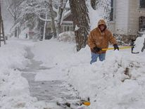Lisa Schultz shovels her sidewalk during a winter storm in Baraboo, Wisconsin