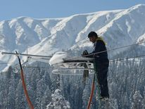 A Kashmiri electrician adjusts an electric wire in Gulmarg, about 55 kms north of Srinagar, on December 13, 2012