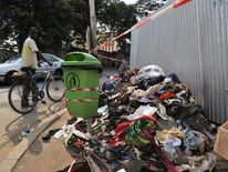 A man walks by a pile of abandoned shoes and clothing