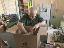 Volunteer unpacking cardboard box at foodbank at St Andrew's Community Centre in north Liverpool