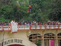 Indian stuntman Sailendra Nath Roy is watched by onlookers as he hangs on a rope while attempting to cross the River Teesta on the outskirts of Siliguri