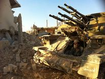 Syrian army soldier sits in his tank in Qusayr