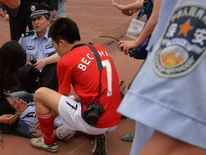Students and security personnel are injured as fans of David Beckham charge forward to catch a glimpse of their idol