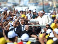 The Pope arrives in Lampedusa - just as hundreds of immigrants were escorted to land by the coast guard.