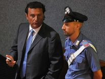 Costa Concordia's captain Francesco Schettino speaks with a policeman