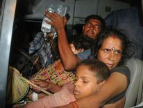 An Indian family with their son who fell ill after consuming a free school meal