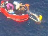 People climb into a rescue boat