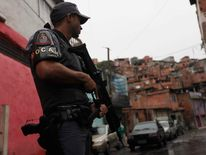 A police officer patrols in the Brasilandia favela during a security operation in Sao Paulo