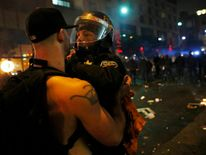 A police officer confronts a rioter