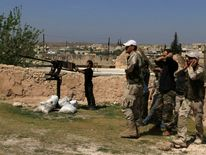 Rebel fighters cover ears as fellow fighter prepares to fire anti-aircraft weapon in Heesh village in Idlib