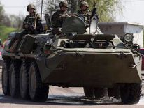 Ukrainian security personnel ride on top of an armoured personnel carrier at a checkpoint near the town of Slaviansk