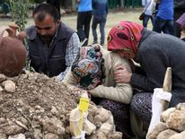 Relatives of a miner mourn beside his grave after a mining disaster in Soma