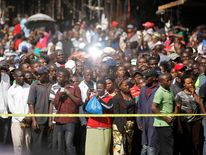 Second-hand clothes traders gather at the scene of a twin explosion at the Gikomba open-air market in Nairobi