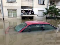 Men sit on a car porch during heavy floods in Bosanski Samac