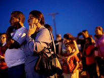 Residents watch investigators inspect the scene of a U.S. military jet crash in Imperial, California.