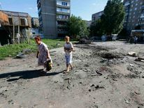 Local residents walk past a crater after shelling in Slaviansk in eastern Ukraine