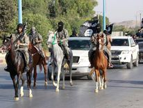 Militant Islamist fighters ride horses as they take part in a military parade along the streets of Syria's northern Raqqa province