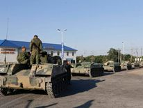 Russian military personnel sit atop armoured vehicles outside Kamensk-Shakhtinsky