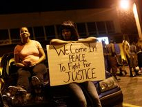 Demonstrators protesting the shooting death of Michael Brown rest on a car while holding a sign in Ferguson