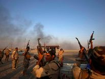 Iraqi Shiite militia fighters fire their weapons as they celebrate breaking a long siege of Amerli by Islamic State militants