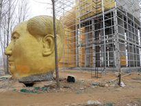 A discarded head is placed on the ground next to a giant statue of Chinese late chairman Mao Zedong under construction near crop fields in a village of Tongxu county