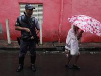A police officer patrols a street as a resident looks on during a security operation in the Brasilandia favela