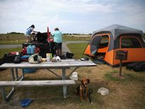 Mark Horrell (C), his wife Lisa Horell (L) and son Haden, break down their campsite and load their vehicle at the Oregon Inlet camp grounds, on July 2, 2014 in Oregon Inlet, NC