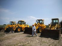 Ronald Hill prepares front end loaders if needed to clear sand covered roads due to approaching storm, on July 2, 2014 in Oregon Inlet, North Carolina.