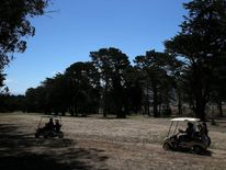 Golfers ride in golf carts next to dry grass on a fairway at Gleneagles Golf Course on July 11, 2014 in San Francisco, California.