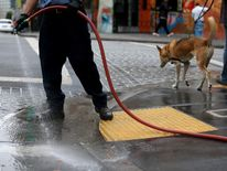 A worker uses a hose to wash the sidewalk in front of a residential hotel on July 15, 2014 in San Francisco, California.