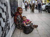 A Syrian refugee begs with her child in downtown Istanbul